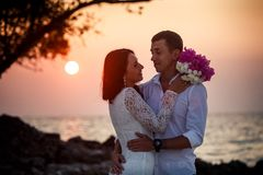 Bride and groom hug at  beach at dawn Stock Photography
