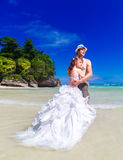 Bride and groom hug on the beach on the tropical island. Stock Photography