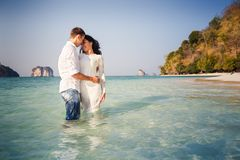 Bride and groom hug half in transparent water Stock Images