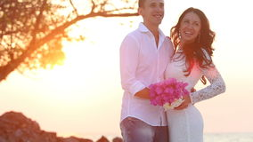 Bride and groom hug and laugh at sand beach at sunrise stock video footage