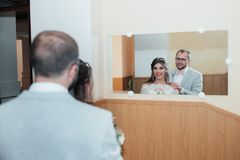 Bride and groom hug and look in their reflection in the mirror.  royalty free stock image