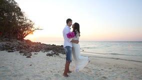 Bride and groom hug at sand beach at sunrise. Brunette bride and handsome groom barefoot hug at sand beach at sunrise stock footage