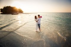 Bride and groom hug in sea Stock Photography