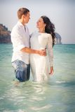 Bride and groom hug in sea Stock Image
