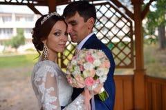 Bride and groom huggin insude summer house Stock Photos