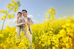 Bride and Groom hugging. Newly-married couple in a rape field Stock Image