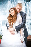 Bride and groom hugging against fountain in park Royalty Free Stock Image
