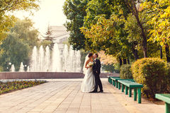 The bride and groom are hugging each other against. The backdrop of the fountain Royalty Free Stock Images