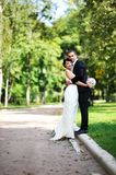 Bride and groom hugging each other gently. During a walk in the summer park Stock Photo