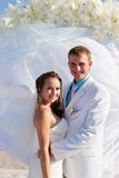 Bride and groom hugging in front of arch royalty free stock image