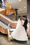 Bride and groom hugging and kissing while standing on the stairs. Wedding, gentle embrace of men and woman. The family, the husband and wife Royalty Free Stock Photography