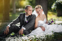 Bride and groom hugging and looking in the eyes of one another sitting at a green grass Stock Photography