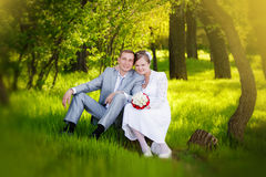 Bride and groom hugging and looking in the eyes of one another sitting at a green grass Royalty Free Stock Photography