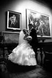 Bride and groom hugging at museum against paintings Royalty Free Stock Photography