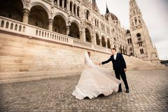 Bride and groom hugging in the old town street. Wedding couple walks in Budapest near Parliament House royalty free stock photo