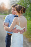 Bride and groom are hugging on the road in spring Royalty Free Stock Photo