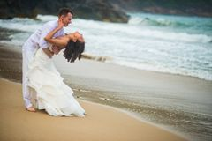 Bride and groom hugging at the sea. couple in love on deserted beach stock photos