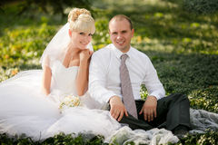 Bride and groom hugging and  sitting at a green grass Stock Photo