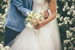 Bride and groom hugging in wedding day with bouquet stock photography