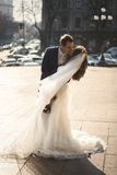Bride and groom hugging at windy day on city street Royalty Free Stock Photography