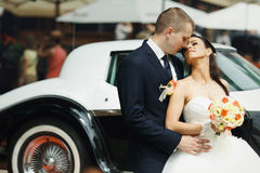 Bride and groom hugs in the front of old car Royalty Free Stock Photo
