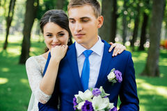 Bride and groom hugs in the park. Bride embraces the groom. Couple in love at wedding day Stock Images
