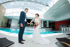 Bride and groom idoors at the pool Stock Images