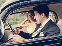 Bride and groom inside a classic car, vintage tone Stock Image