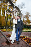 Bride and groom about iron figure on autumn Royalty Free Stock Images