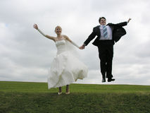 Bride and groom jump Stock Photo