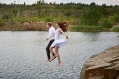 Bride and groom jumping together into the water Stock Image