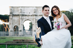 Bride and groom with & x27;Just Married& x27; written on shoe soles, Arco. Di Costantino in the background, Rome, Italy. Selective focus Royalty Free Stock Photos