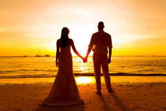 The bride and groom are kept hands on a tropical beach . Silhouette photo at sunset . The bride and groom are kept hands on a tropical beach . Silhouette photo stock photo