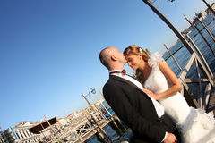Bride and groom kiising in port Stock Images