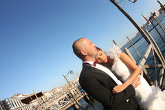 Bride and groom kiising in port Stock Photo
