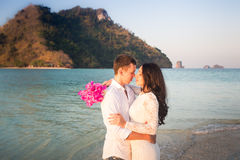 bride and groom kiss against rocky island Royalty Free Stock Photos