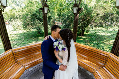 The bride and groom kiss in the arbour. Wedding couple in love at wedding day Stock Photo