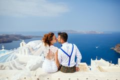 Bride and groom  kiss on the background of the sea. Bride and groom sit together and kiss on the background of the sea, Santorini island, Greece royalty free stock photography