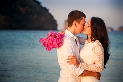 Bride and groom kiss at  beach at dawn Royalty Free Stock Image