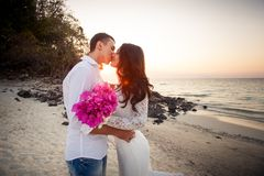 Bride and groom kiss at beach at dawn Royalty Free Stock Photos