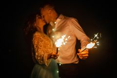 Bride and groom kiss and burn Bengal lights at night. Closeup. Bride and groom kiss and burn Bengal lights next to garland of glowing light bulbs at night royalty free stock photos