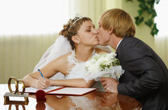 Bride and groom kiss during ceremony of marriage Stock Photos