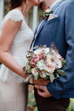 Bride and groom Kiss each other  holding wedding bouquet toge Royalty Free Stock Images
