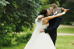 Bride and groom kiss hiding their faces behind the tennis-racket Royalty Free Stock Photos
