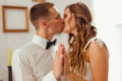 Bride and groom kiss while holding their palms together Stock Photos