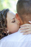 Bride and groom kiss. The bride kisses the groom on the cheek closeup Royalty Free Stock Photography