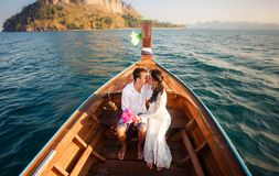 Bride and groom kiss in longtail boat Stock Photography