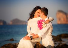 Bride and groom kiss on rock at beach Royalty Free Stock Photo