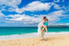 Bride and groom kiss on a tropical beach Stock Photos