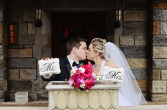 Bride and Groom kissing. A groom and bride kissing and holding Mr. and Mrs. signs Royalty Free Stock Photo